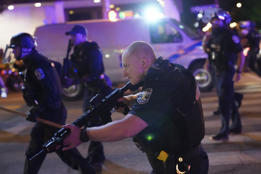 Police move after a Louisville Police officer was shot, Wednesday, Sept. 23, 2020, in Louisville, Ky. A grand jury has indicted one officer on crimina...