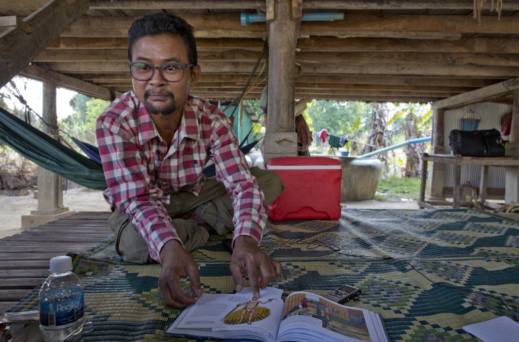 Vannak Anan Prum, who was double trafficked, points to his illustration of an abusive former boss, a palm oil estate owner, in his graphic novel depic...
