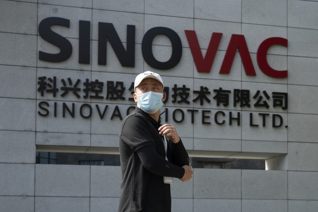 A worker passes by the logo outside the SinoVac vaccine factory in Beijing on Thursday, Sept. 24, 2020. SinoVac, one of China's pharmaceutical compani...