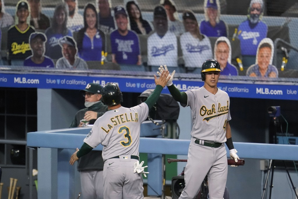 Oakland Athletics' Tommy La Stella (3) is high-fived by Jake Lamb after La Stella scored on a double by Robbie Grossman during the first inning of the...