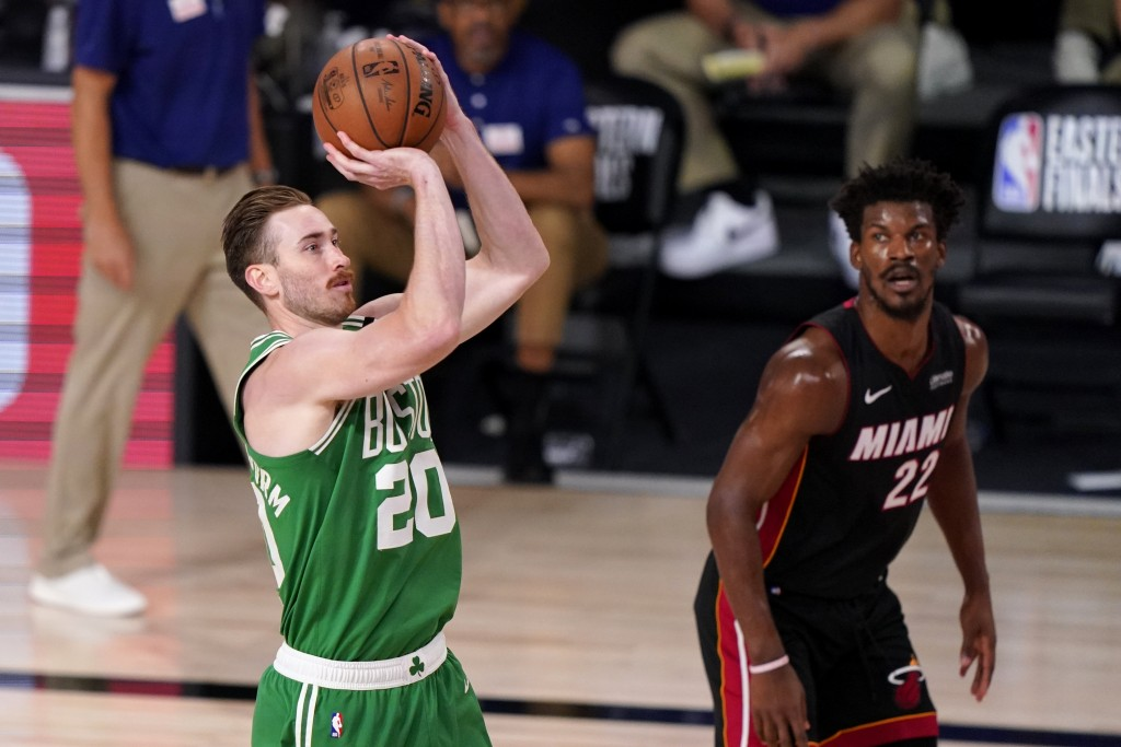Boston Celtics forward Gordon Hayward (20) takes a shot as Miami Heat's Jimmy Butler (22) looks on during the second half of Game 4 of an NBA basketba...