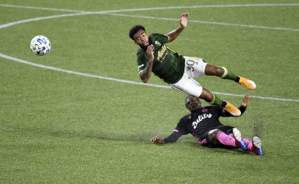 Portland Timbers midfielder Eryk Williamson, left, is upended by Seattle Sounders defender Nouhou Tolo during the first half of an MLS soccer match in...