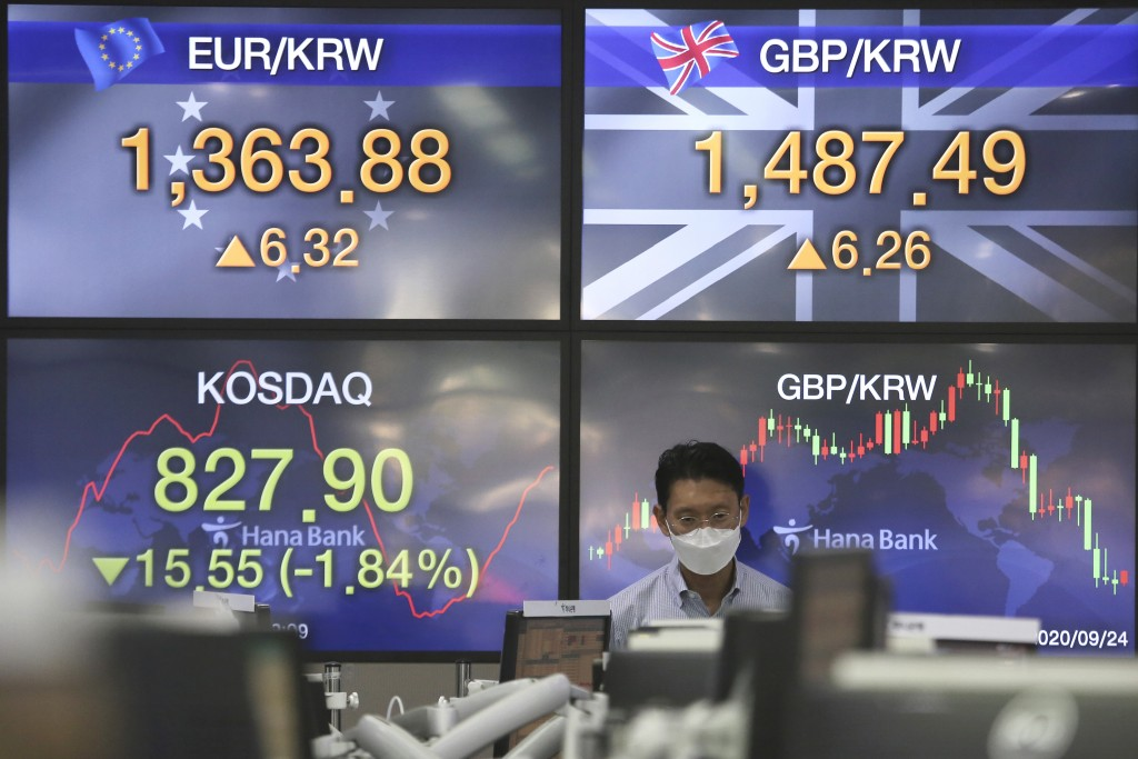 A currency trader watches monitors at the foreign exchange dealing room of the KEB Hana Bank headquarters in Seoul, South Korea, Thursday, Sept. 24, 2...
