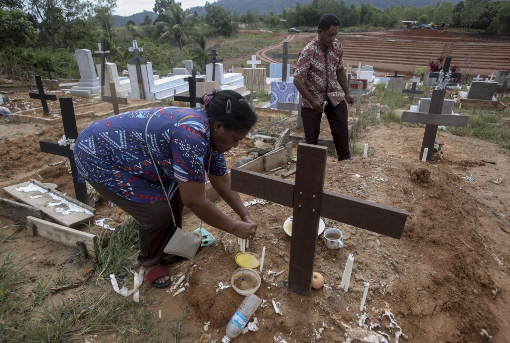 An Indonesian migrant worker places candles on the grave of her husband who worked on a Malaysian palm oil plantation in Sabah, Malaysia, on Sunday, D...