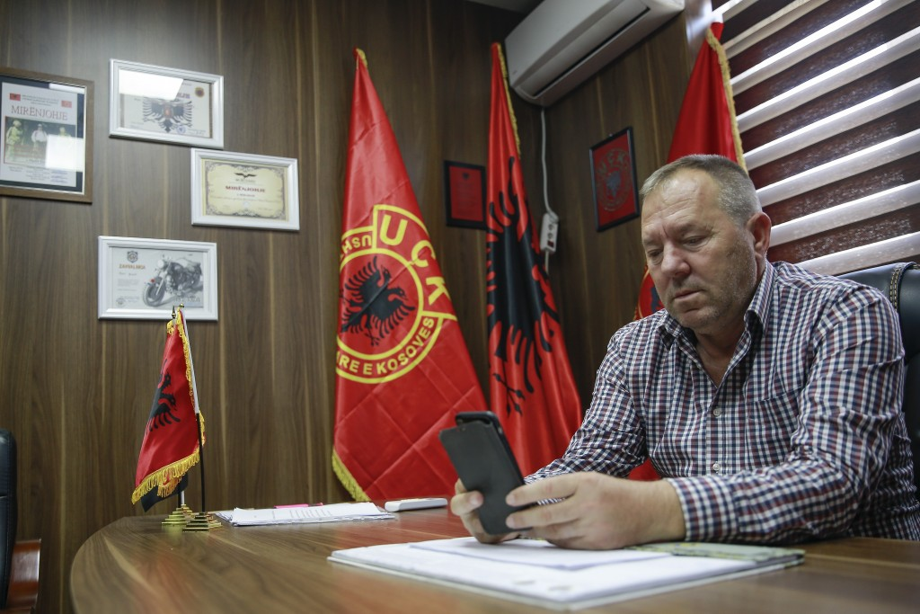 Hysni Gucati head of the War Veterans Organization of the Kosovo Liberation Army looks at a photo of his co-fighter former Kosovo Liberation Army comm...