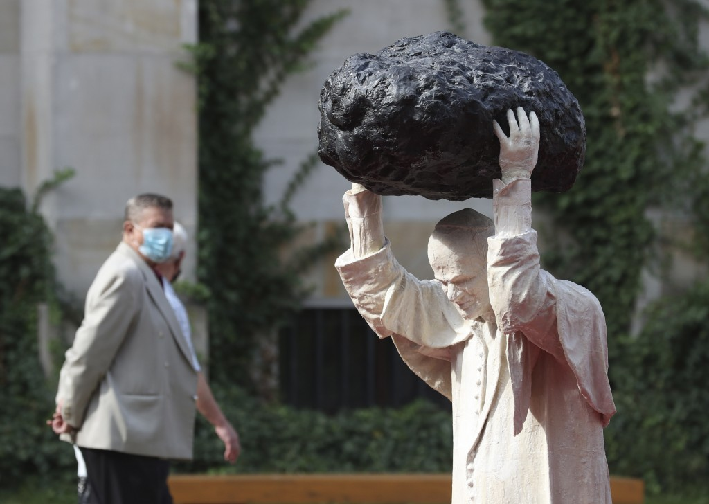 """A visitor to the National Museum walks past a new statue of the late pope, St. John Paul II, throwing a stone at a """"Poisoned Well"""" just hours before i..."""