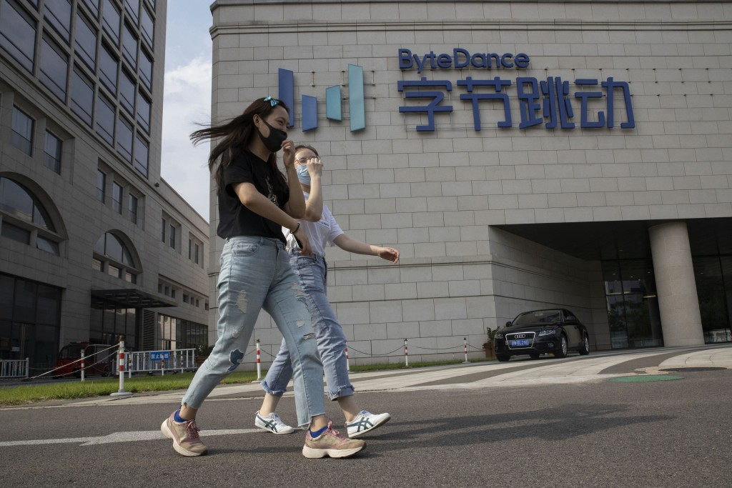 FILE - In this Aug. 7, 2020, file photo, women wearing masks to prevent the spread of the coronavirus chat as they pass by the headquarters of ByteDan...