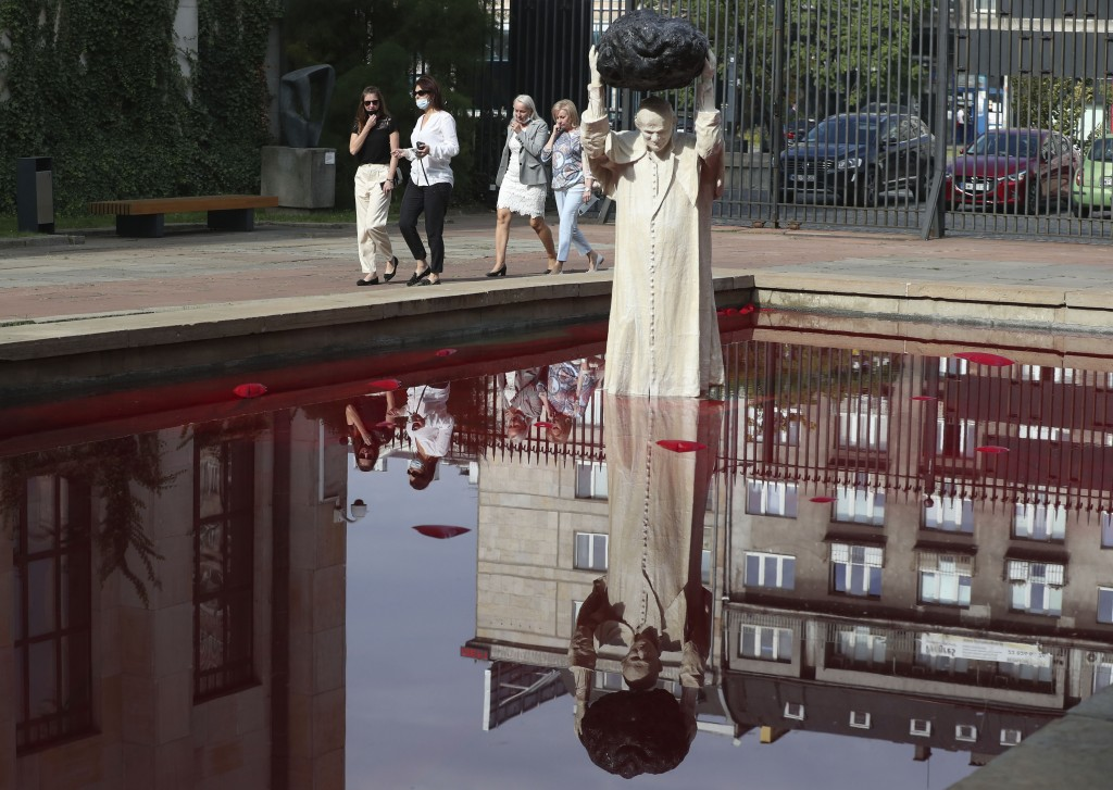 """Visitors to the National Museum walk past a new statue of the late pope, St. John Paul II, throwing a stone at a """"Poisoned Well"""" just hours before its..."""