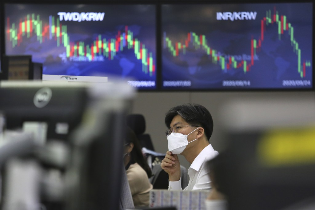 A currency trader adjusts his face mask at the foreign exchange dealing room of the KEB Hana Bank headquarters in Seoul, South Korea, Thursday, Sept. ...