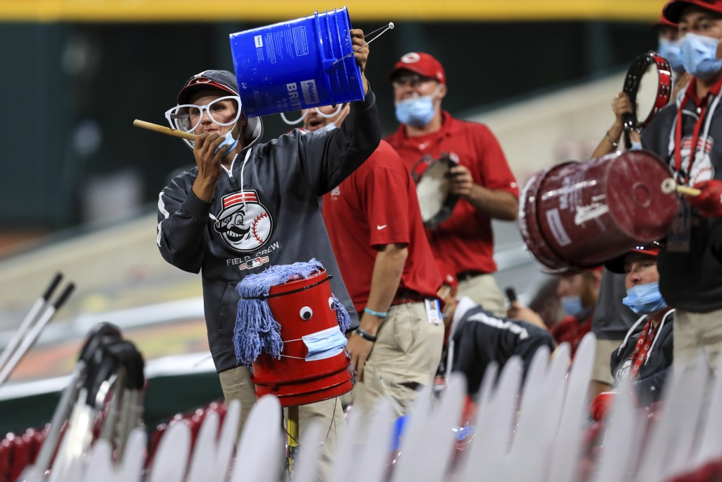 Members of the Reds' grounds crew acknowledge Cincinnati Reds' Trevor Bauer as he stands in the dugout in the ninth inning during a baseball game betw...