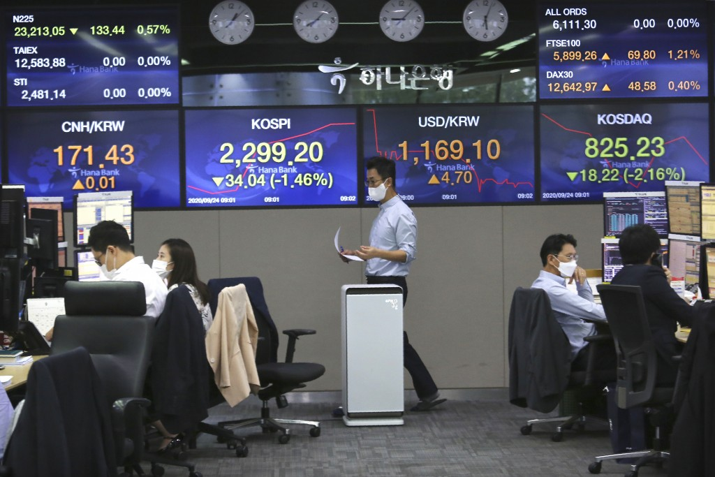 A currency trader walks by screens showing foreign exchange rates at the foreign exchange dealing room of the KEB Hana Bank headquarters in Seoul, Sou...