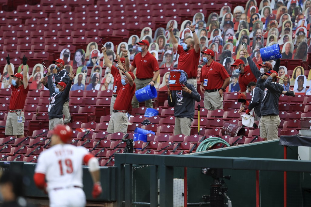 Members of the Cincinnati Reds' grounds crew react as Reds' Joey Votto runs the bases after hitting a two-run home run during the first inning of the ...