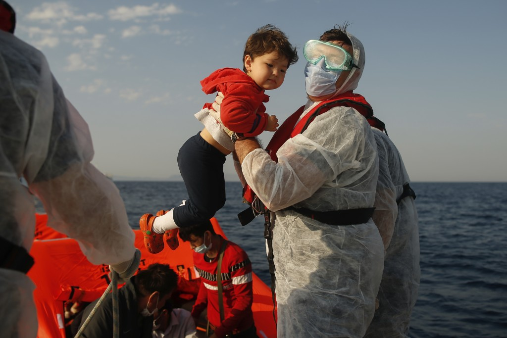A Turkish coast guard officer, wearing protective gear to help prevent the spread of coronavirus, carries a child off a life raft during a rescue oper...
