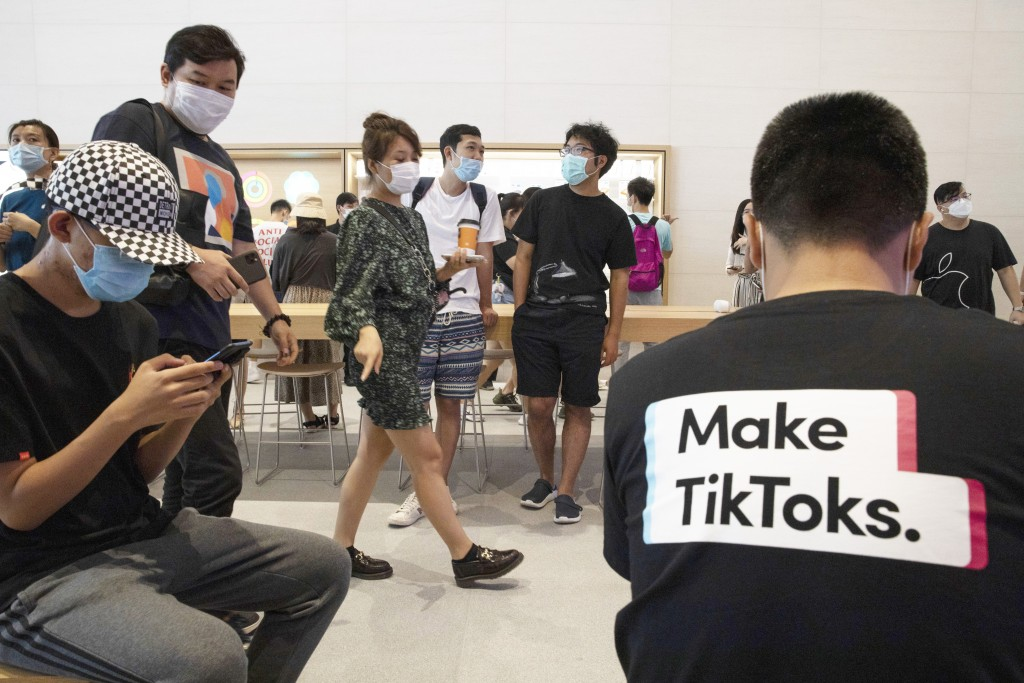 In this July 17, 2020, file photo, a visitor to an Apple store wears a t-shirt promoting Tik Tok in Beijing. TikTok executives told a Senate committee...