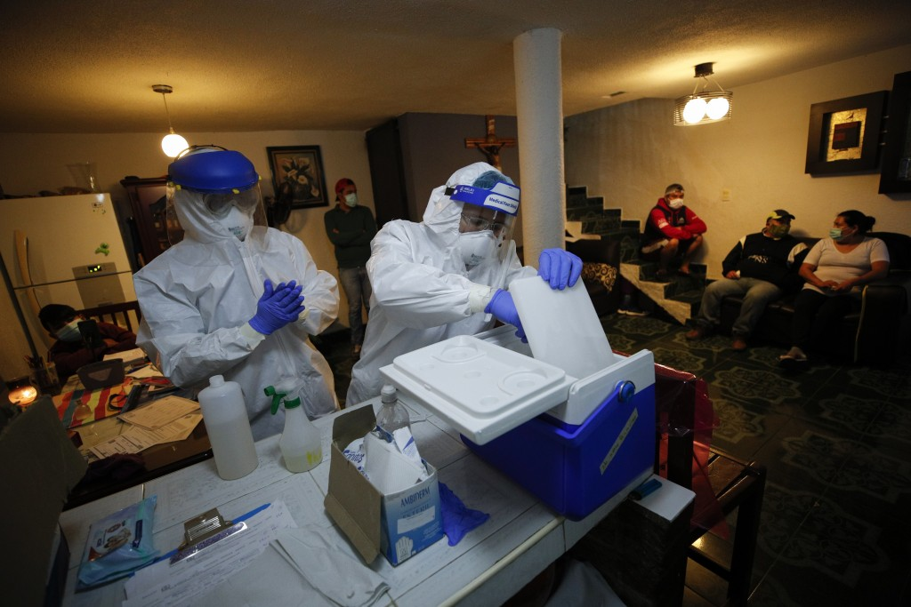 Nurse Alejandro Ramirez, center, prepares material for Dr. Ivan Mandujano as they conduct COVID-19 tests on seven members of the Moreno family, in the...