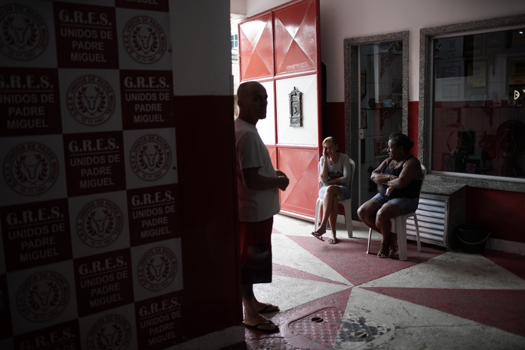 """Members of the Unidos de Padre Miguel samba school chat at the """"quadra"""" or court entrance, where float construction, costume sewing and dance rehearsa..."""