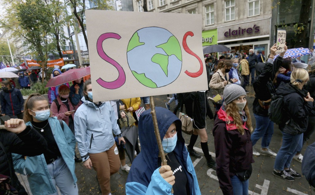 Environmental activists wearing face masks to help protect against the spread of the coronavirus stage during a rally marking the Global Day of Climat...