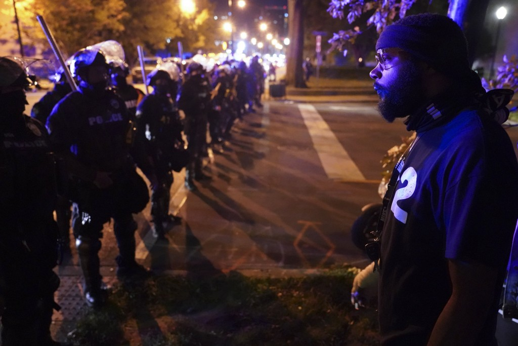 Police speak with protesters at the First Unitarian church, Thursday, Sept. 24, 2020, in Louisville, Ky. Authorities pleaded for calm while activists ...