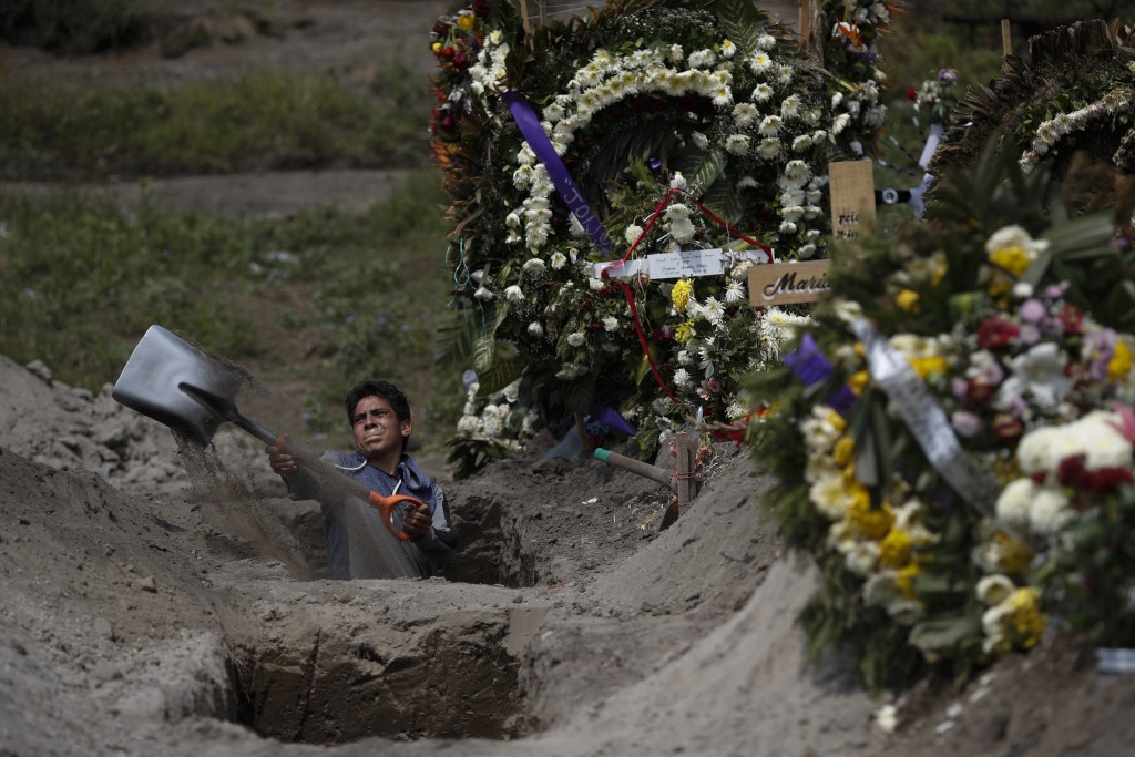 A cemetery worker digs a grave in a section of the Valle de Chalco Municipal Cemetery which opened early in the coronavirus pandemic to accommodate th...