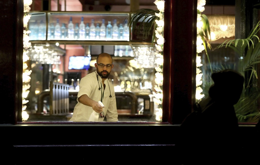 A barman at the Seven Stars pub in Brighton, England, cleans the bar area after closing by 10 p.m. per the curfew Thursday, Sept. 24, 2020. To control...