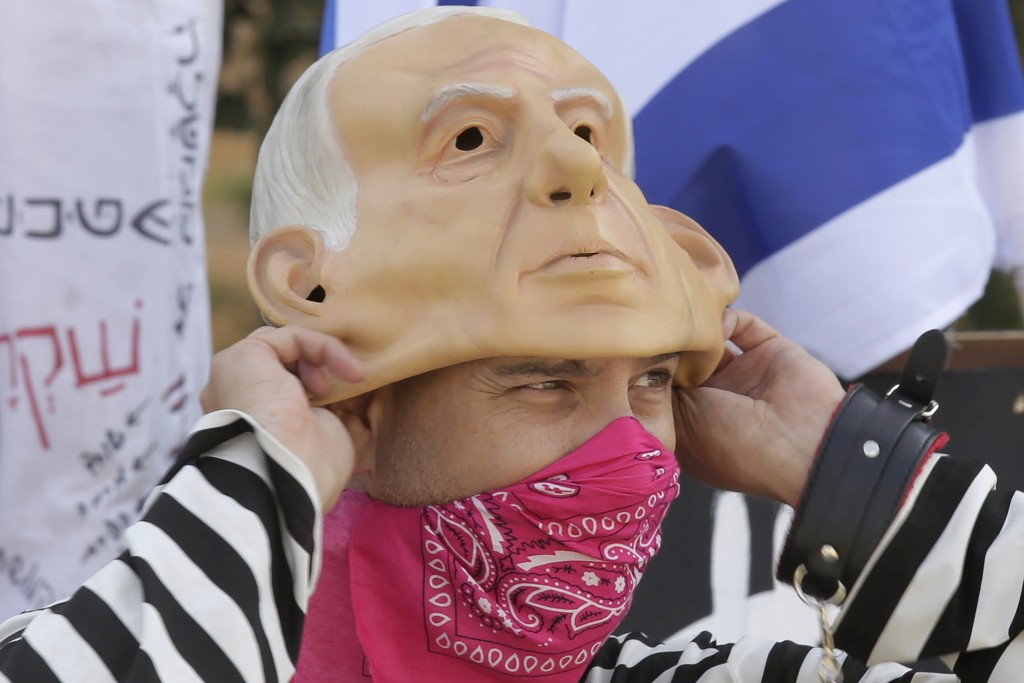 A protester wears a bandana as a face mask as he pulls on a rubber mask representing Israeli Prime Minister Benjamin Netanyahu outside of the Knesset ...