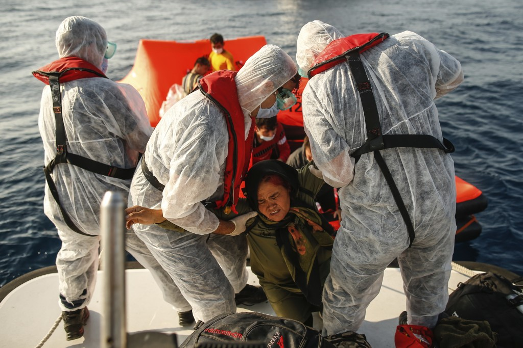 Turkish coast guard officers wearing protective gear to help prevent the spread of coronavirus, carry a woman off a life raft during a rescue operatio...
