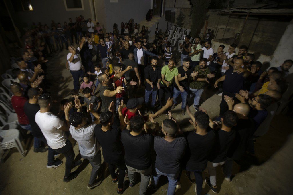 Palestinians celebrate during a wedding party in Azmut near the West Bank city of Nablus, Thursday, Sept. 24, 2020. In a region where marriage is the ...