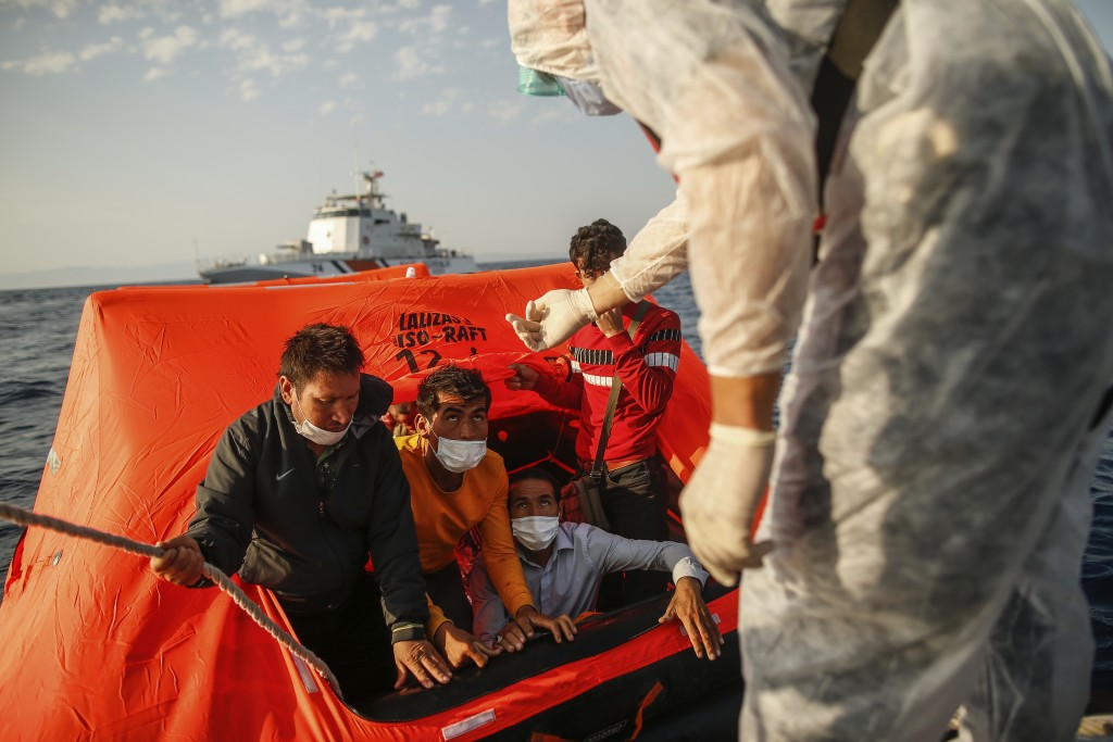 Turkish coast guards officers on their vessel, wearing protective gear to help prevent the spread of coronavirus, talk to migrants on a life raft duri...