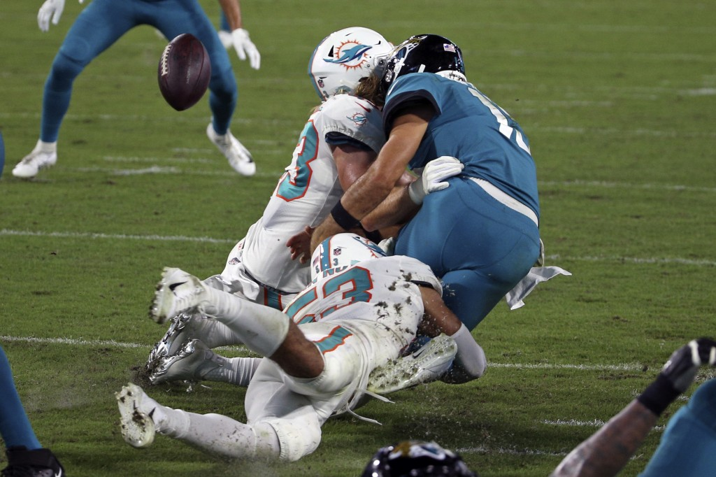 Jacksonville Jaguars quarterback Gardner Minshew, right, fumbles the ball as he is hit by Miami Dolphins outside linebacker Andrew Van Ginkel, left, a...
