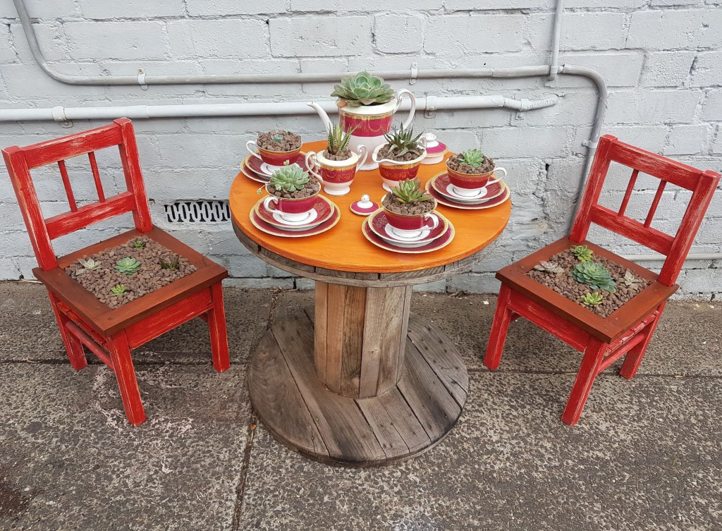 In this May 24, 2020 photo provided by Rick Everett, a small table decorated with succulents sits below a window where Everett offers free coffee and ...