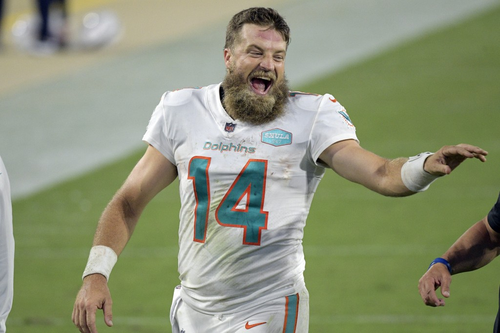 Miami Dolphins quarterback Ryan Fitzpatrick laughs with coaches as he comes off the field after defeating the Jacksonville Jaguars in an NFL football ...