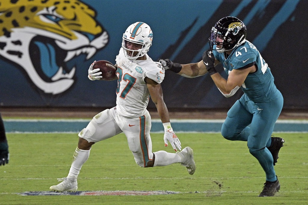 Miami Dolphins running back Myles Gaskin, left, runs past Jacksonville Jaguars middle linebacker Joe Schobert (47) during the first half of an NFL foo...