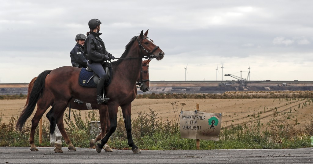 Police officers on horses secure the Garzweiler surface coal mine, passing a sign reading 'climate activism is not a crime' near Keyenberg, Germany, F...