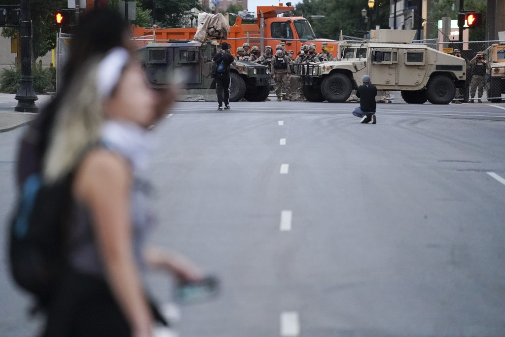 Members of the Kentucky National Guard watch people in the street, Thursday, Sept. 24, 2020, in Louisville, Ky. Authorities pleaded for calm while act...
