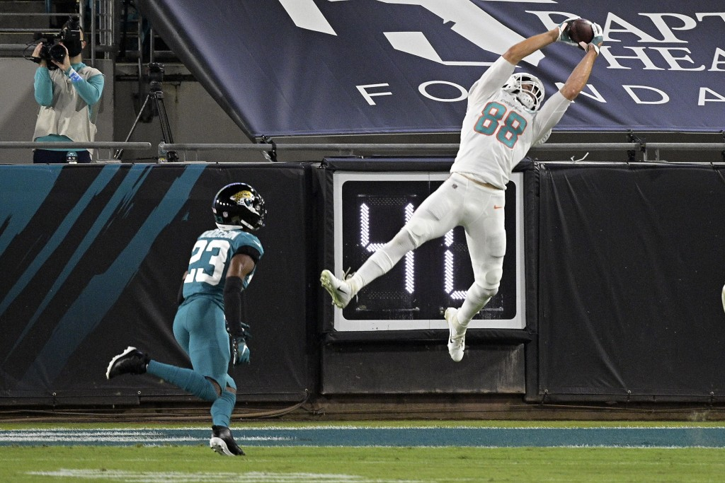 Miami Dolphins tight end Mike Gesicki (88) makes a reception in front of Jacksonville Jaguars cornerback C.J. Henderson (23) during the first half of ...