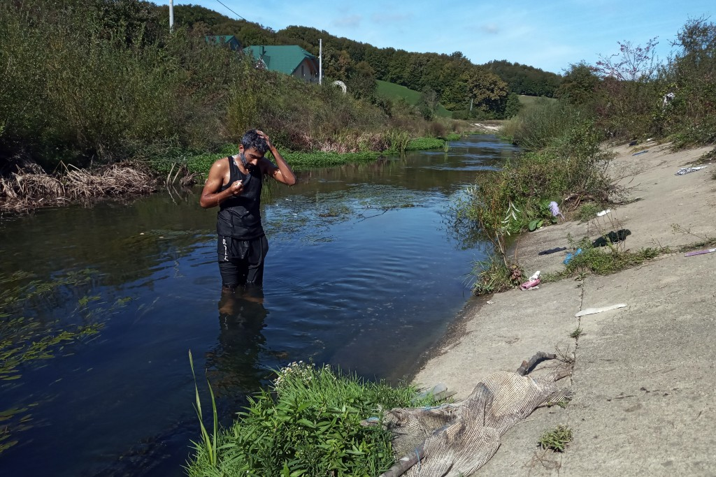 A migrant washes himself in a river near the Croatian border near Kladusa, Bosnia, Thursday, Sept. 24, 2020. A top U.N. official in Bosnia says local ...
