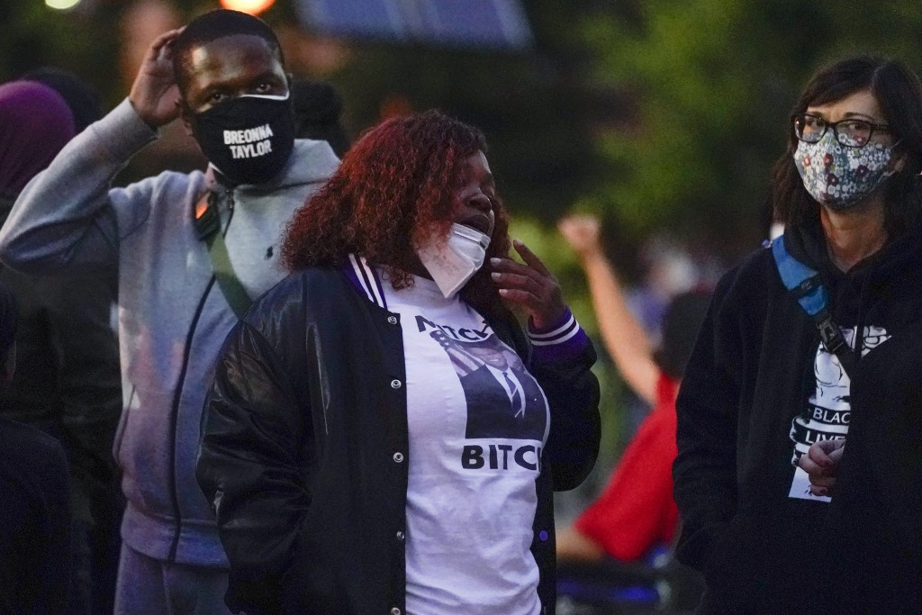 Tamika Palmer, center, the mother of Breonna Taylor stands with demonstrators, Thursday, Sept. 24, 2020, in Louisville, Ky. Authorities pleaded for ca...