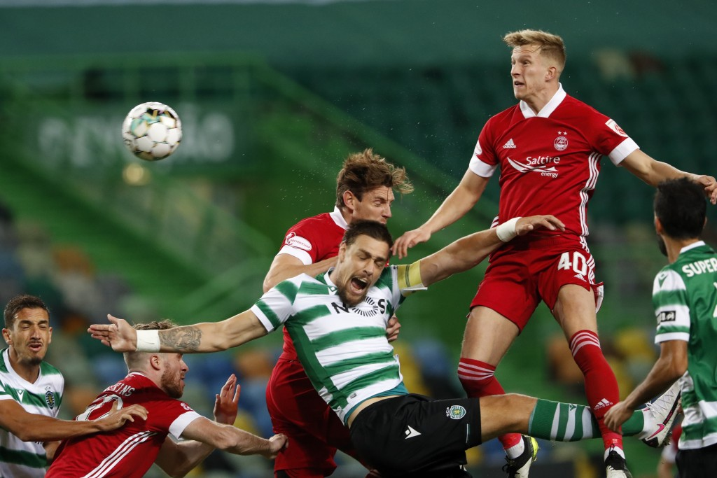 Sporting's Sebastian Coates, center, jumps for the ball with Aberdeen's Ashton Taylor, background and Ross McCrorie, right, during the Europa League t...