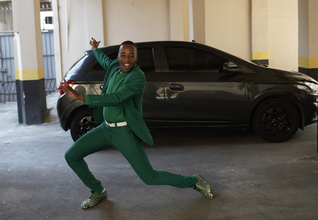 Diogo Jesus, the main dancer for the Mocidade Independente de Padre Miguel samba school, strikes a pose for reporters next to his car, in Rio de Janei...
