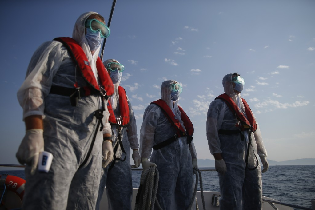 Turkish coast guard officers, wearing protective gear to help prevent the spread of the coronavirus, approach a life raft with migrants during a rescu...