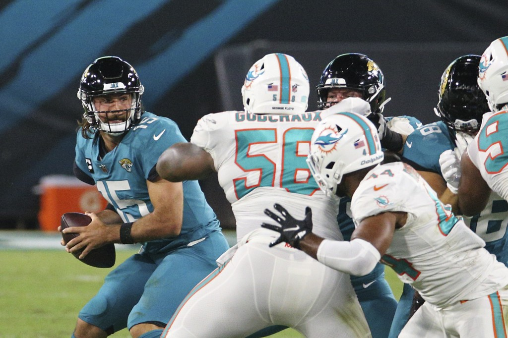 Miami Dolphins defensive tackle Davon Godchaux (56) pressures Jacksonville Jaguars quarterback Gardner Minshew, left, as he looks for a receiver durin...