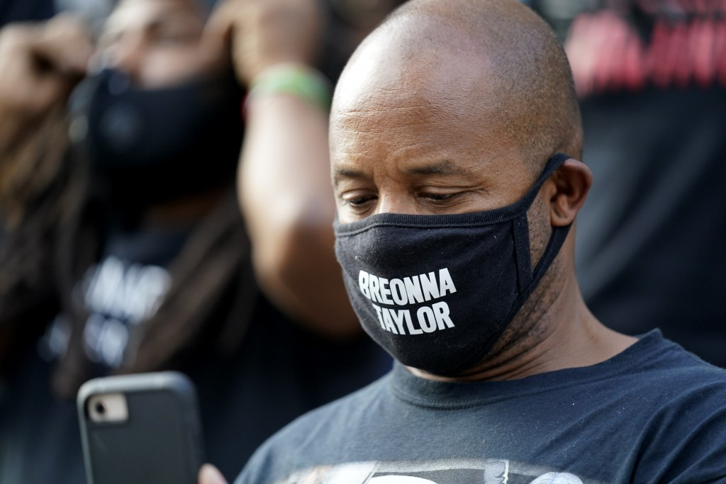 A man views his phone, Thursday, Sept. 24, 2020, in Louisville, Ky. Authorities pleaded for calm while activists vowed to fight on Thursday in Kentuck...