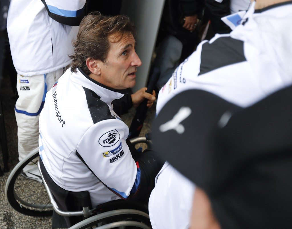 FILE - In this Sunday, Jan. 27, 2019 filer, Alex Zanardi talks with crew members in his pit stall during the IMSA 24-hour race at Daytona Internationa...