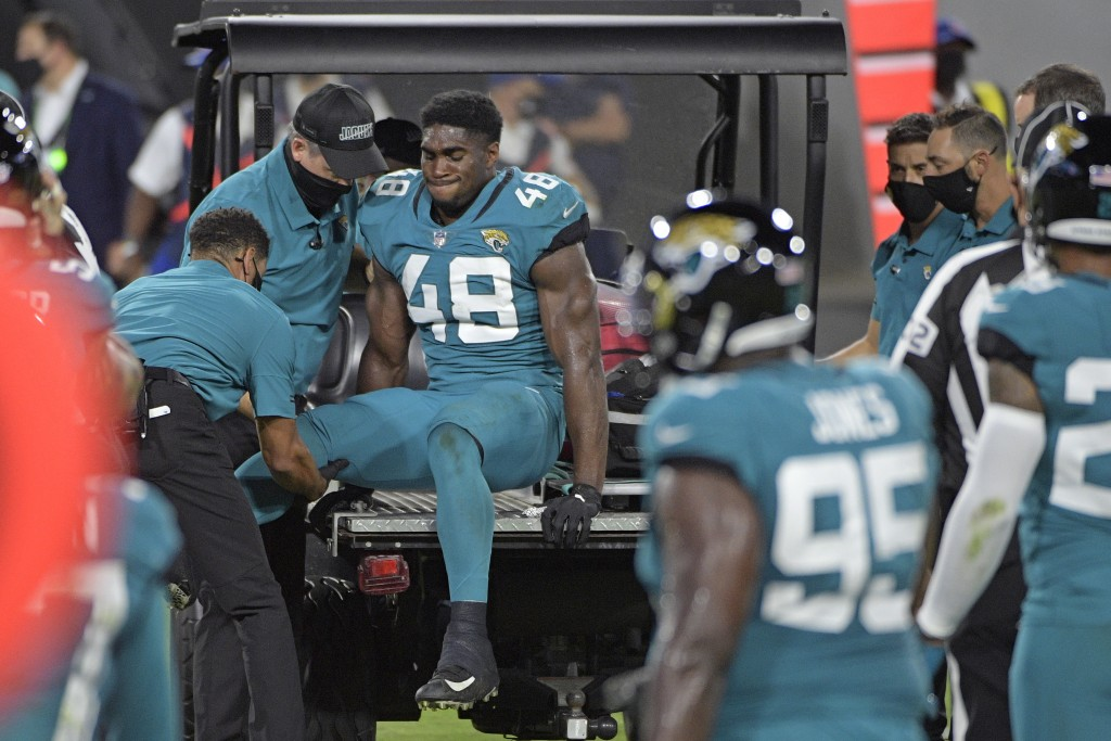 Teammates watch as Jacksonville Jaguars outside linebacker Leon Jacobs (48) is taken off the field after he was injured during the first half of an NF...