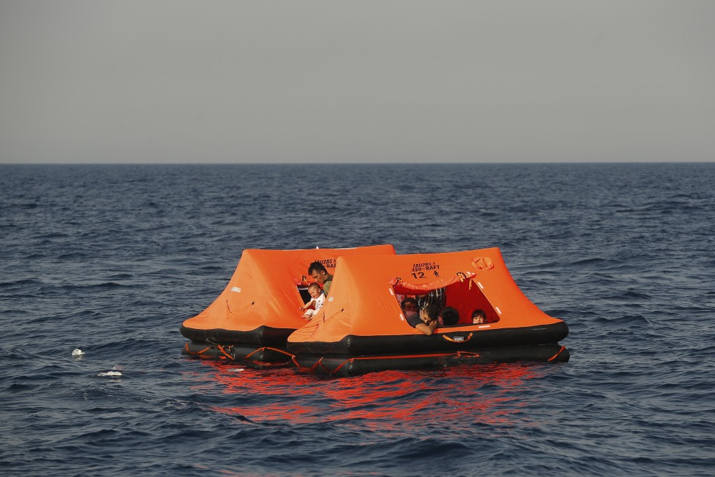 Afghan migrants watch from inside a life raft during a rescue operation by the Turkish coast guard, in the Aegean Sea, between Turkey and Greece, Satu...