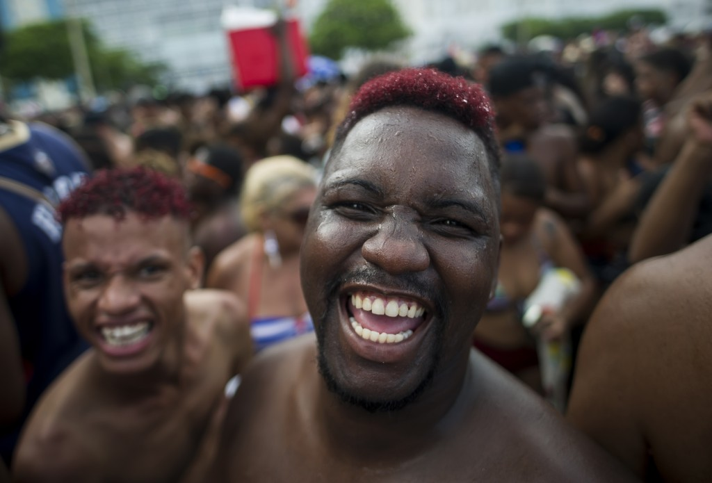 """FILE - in this Jan. 12, 2020 file photo, revelers smile as they look on the camera during the """"Bloco da Favorita"""" street party on Copacabana beach, Ri..."""