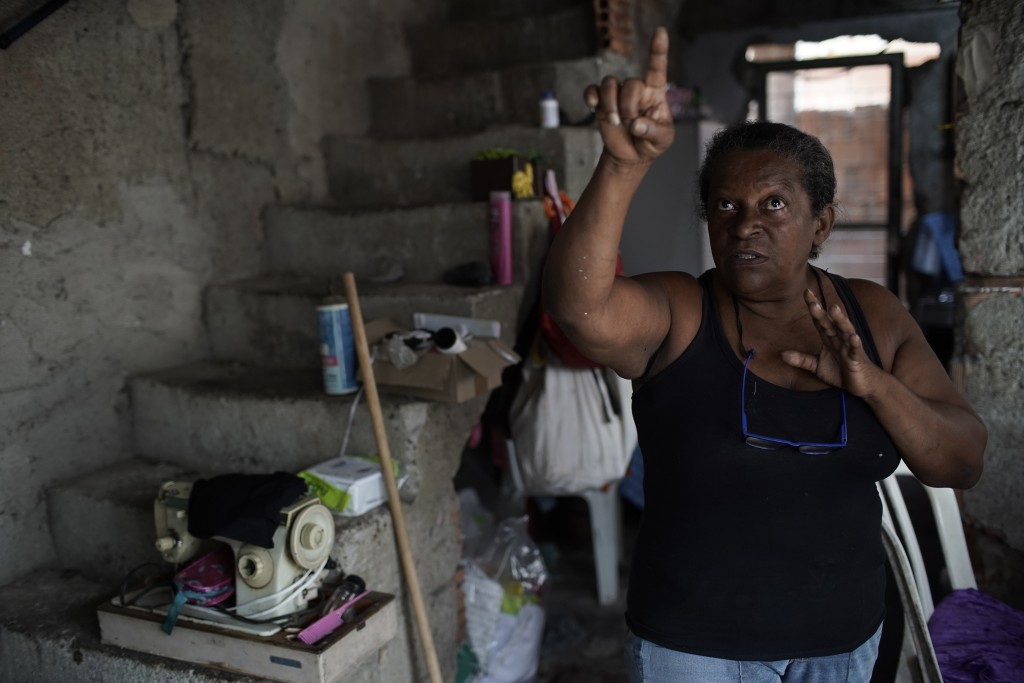 Seamstress Vania da Silva, 62, a member of the Unidos de Padre Miguel samba school, points to a wall inside her home, damaged by stray bullets, in Rio...