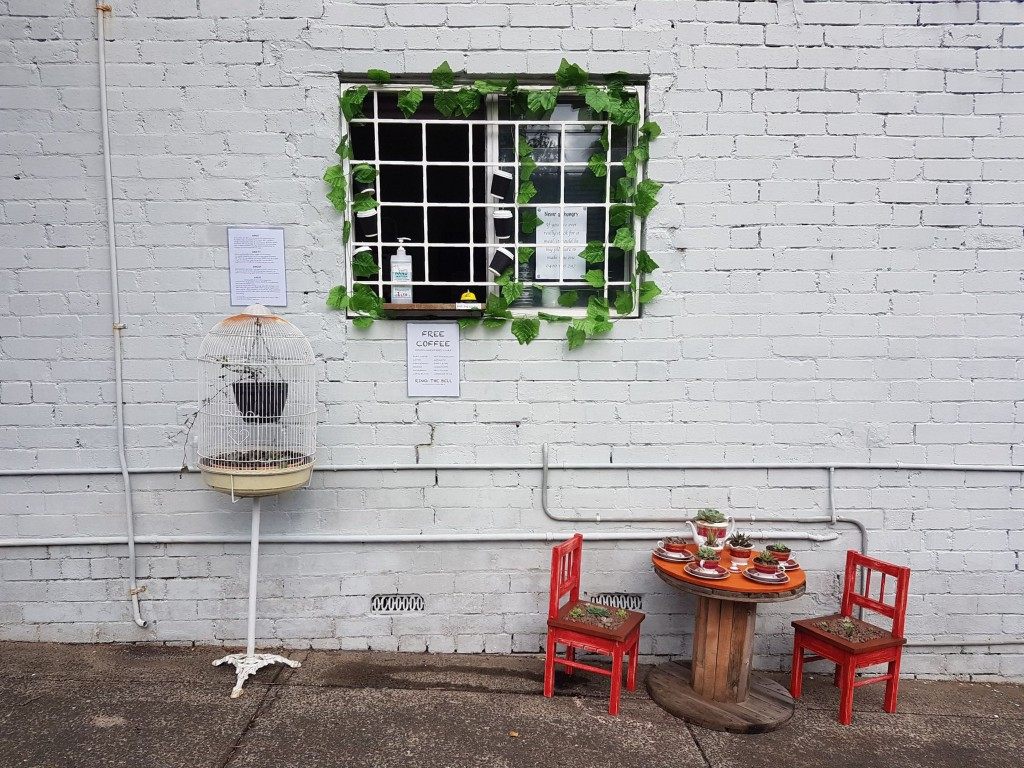In this July 25, 2020 photo provided by Rick Everett, a small table decorated with succulents sits below a window where Everett offers free coffee and...
