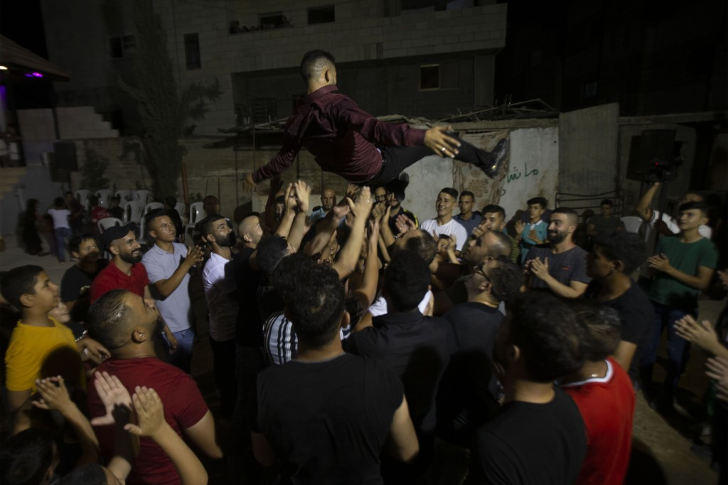 A Palestinian groom is thrown in the air during a wedding party in Azmut near the West Bank city of Nablus, Thursday, Sept. 24, 2020. In a region wher...
