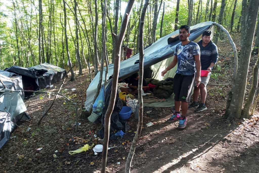 Migrants stand next to their makeshift tent in woods near the Croatian border near Kladusa, Bosnia, Thursday, Sept. 24, 2020. A top U.N. official in B...